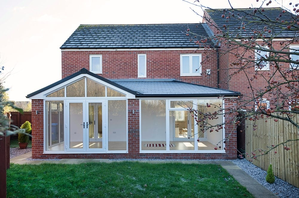 Red Brick House with Black Tiled WARMroof and White Windows