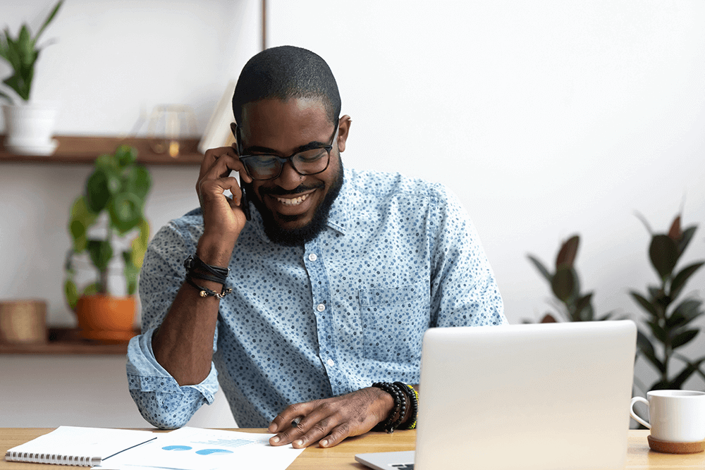 Smiling man on phone with laptop