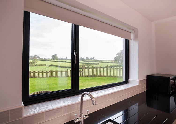 Black aluminium window over sink looking out to garden